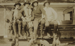 Belle Baruch, far right, with three guests have returned to headquarters at the hunt cabin at Clambank with a few pairs of ducks on display. c. 1910