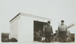 Two of the four Caines brothers in Bernard Baruch's employ, Sawney and Hucks, stand near a shed at Hobcaw's Clambank Landing as they prepare to clean ducks from the day's kill. c. 1919